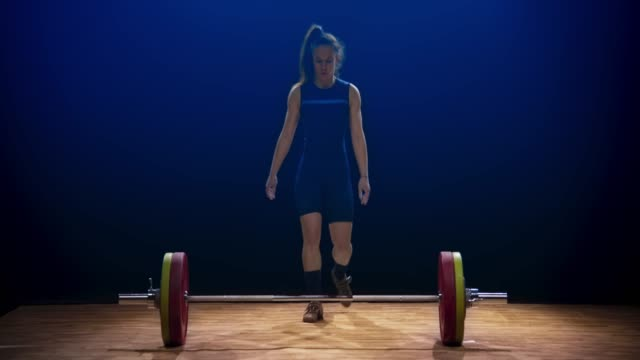 Young female weightlifter lifting the barbell at a competition with a snatch lift
