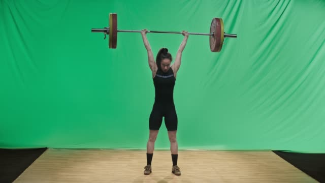 LD Young female weightlifter lifting the barbell performing the clean and jerk lift