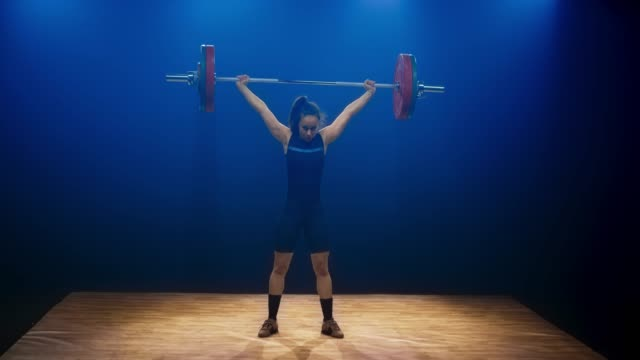 LD Young female weightlifter lifting the barbell with the snatch lift at the competition