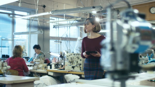 young female with a tablet is walking through a clothing manufactory. - cucire video stock e b–roll