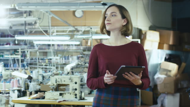 Young female with a tablet is walking through a clothing workshop and meeting employees. video