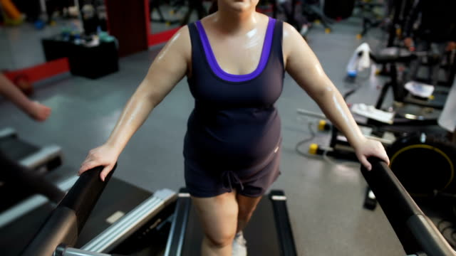 Young female with big belly exercising on treadmill, working hard to lose weight video