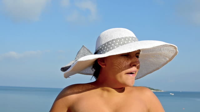 young female with hat in bikini yawning with summer sea horizon at background - young singles stock videos and b-roll footage