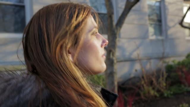 young female woman walking on the street in the sun - walking home sunset street bildbanksvideor och videomaterial från bakom kulisserna