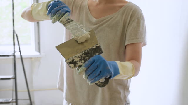 Young female worker preparing putty for the wall repair. Young female worker preparing putty for the wall repair. Close-up video of spreading plaster on metal spatula. cement stock videos & royalty-free footage