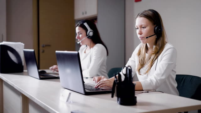 young female workers of call center with gadgets at desk - ассистент стоковые видео и кадры b-roll
