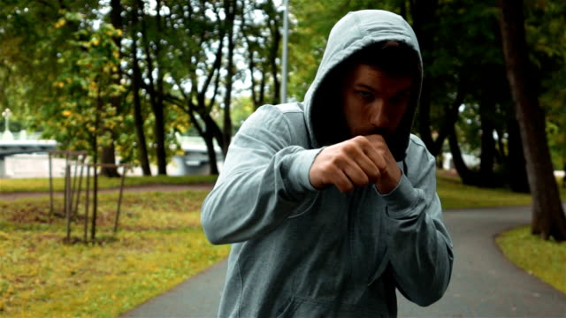 Young fighter in gray hook running at park and brandish hands like boxer video