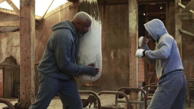 young fighter working out with his coach in an abandoned farm - allenamento con l'ombra video stock e b–roll