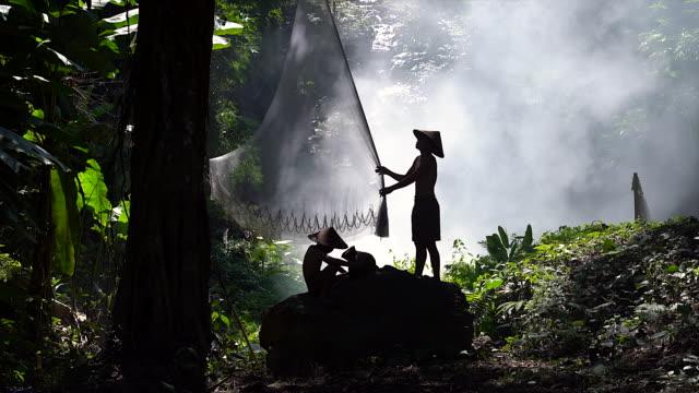 ung fiskare förbereder netto innan fisket netto på berget i djungeln som bakgrund. silhouette ung fiskare utomhus. jordbruk koncept. - madagaskar bildbanksvideor och videomaterial från bakom kulisserna