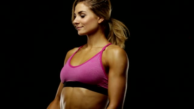 Young fit blond woman with dumbbells posing on black. Young fit blond woman with dumbbells posing on black and shyly looks at the camera. human back stock videos & royalty-free footage