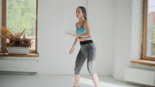 Young fit brunette girl in sportswear does exercises in bright room. Doing sports at home. Healthy lifestyle. Squats Young fit brunette girl in blue top, gray leggings, black sneakers does exercises in bright room. Doing sports at home. Healthy lifestyle. Squats, female raises and lowers her body, slow motion bodyweight training stock videos & royalty-free footage