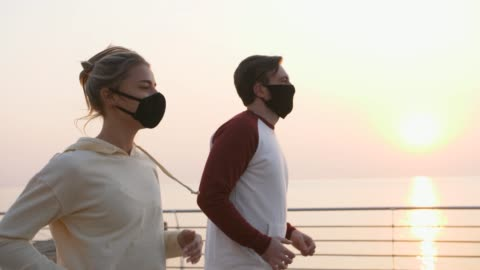 vídeos de stock e filmes b-roll de young fit couple in protective masks running outdoors near the sea during beautiful sunrise, slow motion - exercitar