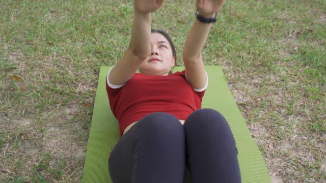 vidéos et rushes de jeune femme asiatique heureuse de forme se asseyent l'exercice à un stationnement local - mince