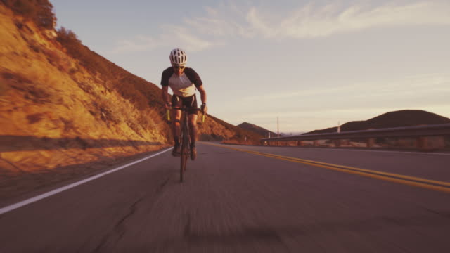 Young Fit Man Cycling On Road Bike Outside At Sunset  Racing Downhill Low fast angle of healthy man road biking on road at sunset biking stock videos & royalty-free footage