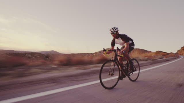 Young Fit Man Cycling On Road Bike Outside At Sunset  Racing Downhill video