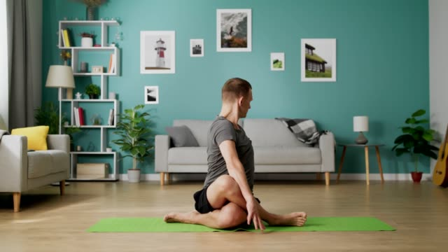 Young fit man on the floor in his living room does different yoga poses video