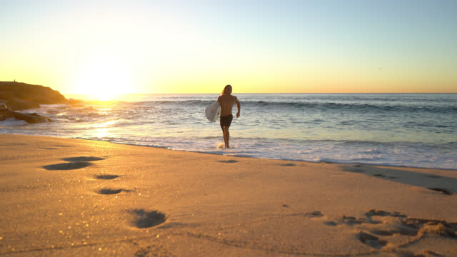 young fit man running back to the beach carrying his surfing board looking very happy - rock formations stock videos & royalty-free footage