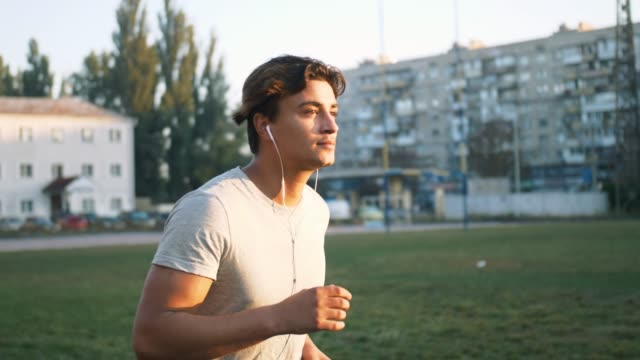 Young fit mixed race man listening to music and working out by running on urban stadium track