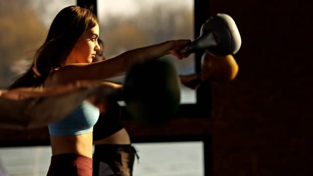 Young fit people having training in the gym Three people are exercising with kettle bell in the gym cross training stock videos & royalty-free footage