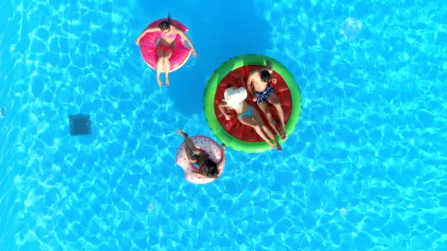 stockvideo's en b-roll-footage met boven naar beneden: jonge mensen ontspannen op opblaasbare watermeloen en ringdiagrammen praalwagens past - opblaasband