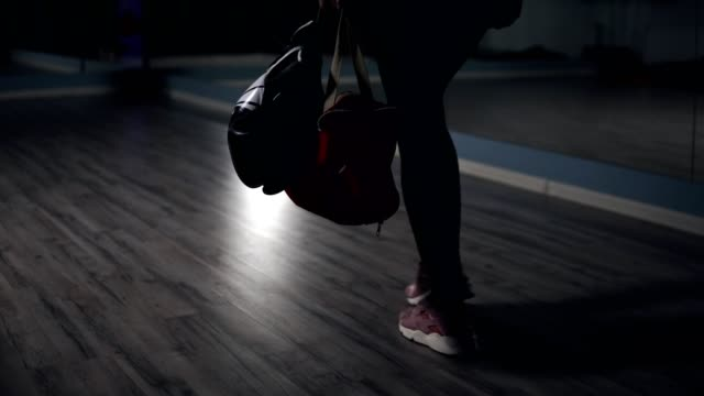 Young fit woman entering a fitness club with a bag and boxing gloves and preparing for the training in a boxing club. Shot in 4k video