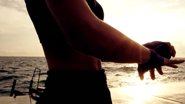 Young fit woman getting her fists ready for the boxing gloves by wrapping bandage around them standing against the sun. Female boxer wrapping hands with boxing wraps on the beach. Lens flare video