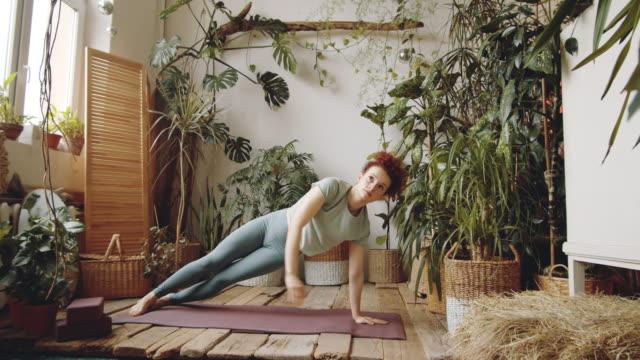 vídeos de stock e filmes b-roll de young fit woman practicing side plank during home yoga workout - treino em casa
