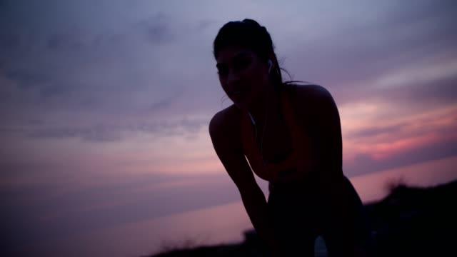 vidéos et rushes de young fit femme avec un casque au repos après jogging au coucher du soleil - joggeuse