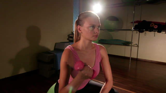 Young fit woman with light dumbbells exercising on fitness ball video
