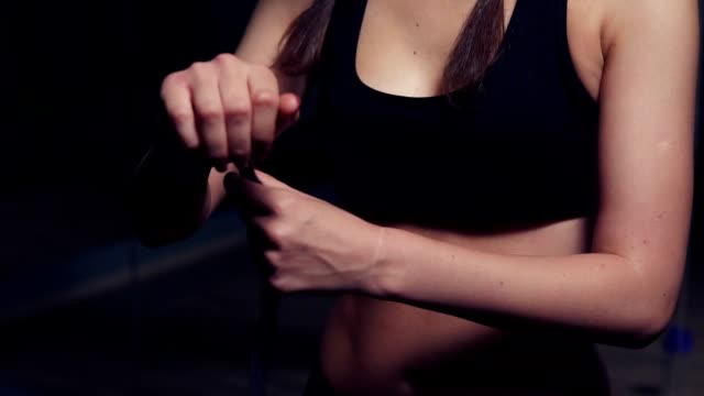 Young fit woman wrapping hands with black boxing wraps in dark room. Slowmotion shot Young fit woman wrapping hands with black boxing wraps in dark room. Slowmotion shot girl power stock videos & royalty-free footage