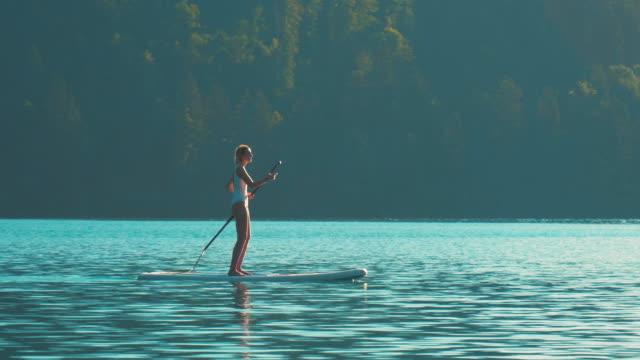 vídeos y material grabado en eventos de stock de una joven chica de fitness con un traje de baño blanco está remando en un remo de pie en el medio del lago bled en una hermosa mañana de verano. - charca