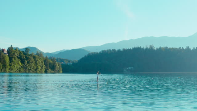 A young fitness girl in white swimwear is paddling on a SUP in the middle of the lake on a beautiful summer morning. video