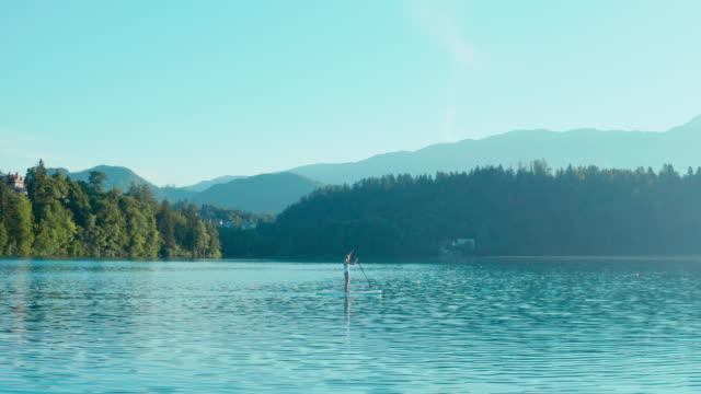 vídeos y material grabado en eventos de stock de una joven chica de fitness con traje de baño blanco está remando en un sup en medio del lago en una hermosa mañana de verano. - charca
