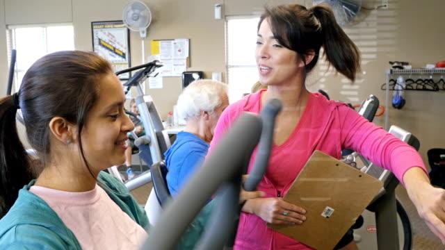 stockvideo's en b-roll-footage met jonge fitness instructeur helpt client in sportschool met fitnessapparatuur - fitnessleraar
