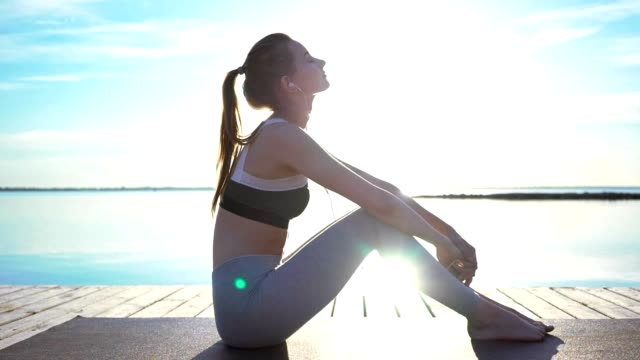Young fitness strong woman sitting near beach listening music with earphones video