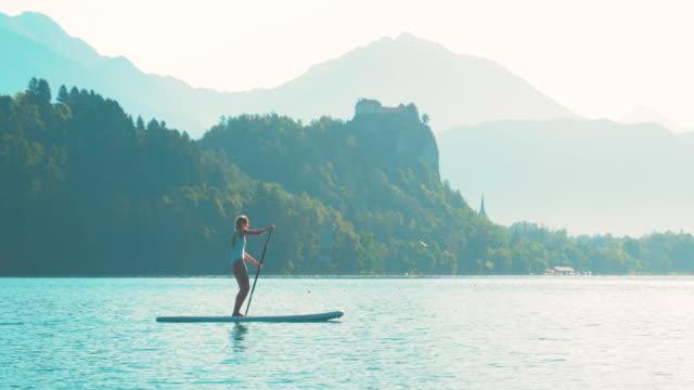 stockvideo's en b-roll-footage met jonge fitness vrouw in witte badmode is peddelen op een sup in het midden van het meer van bled met een kasteel op de achtergrond op een mooie zomer ochtend. - paddle