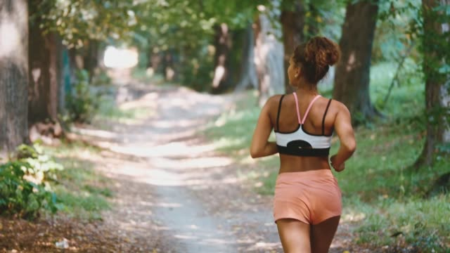 Young fitness woman running at forest trail. Back view