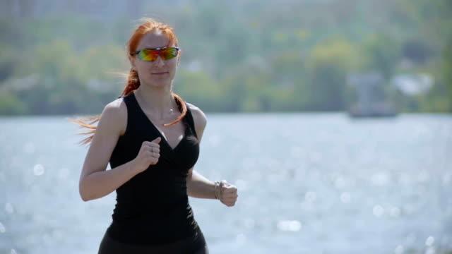 unga fitness kvinna kör i en park, nära floden. kaukasiska modell. slow motion - tävlingsdistans bildbanksvideor och videomaterial från bakom kulisserna