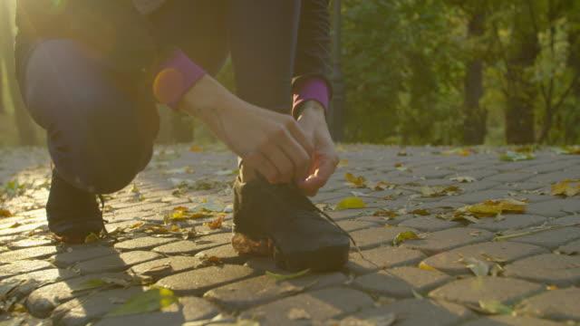 vidéos et rushes de jeune femme de forme physique attachant des baskets exécutant des lacets de chaussure dans le stationnement. - ligoté