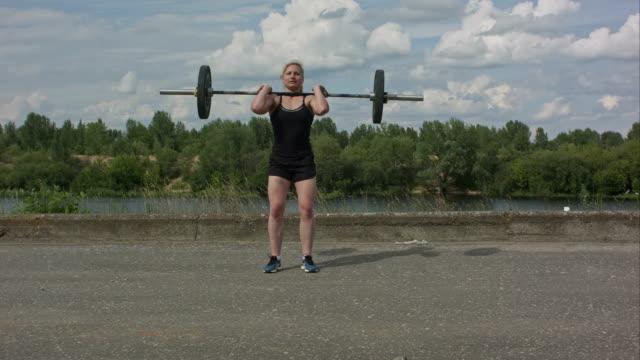 Jonge fitness vrouw uit te werken met halters outdoors video
