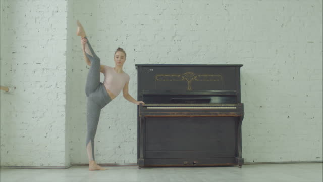 Young flexible woman doing standing split yoga pose Charming flexible woman with perfect body doing standing split yoga pose near piano in dance studio. Pretty graceful sporty female dancer warming up and stretching in standing split before rehearsal. doing the splits stock videos & royalty-free footage