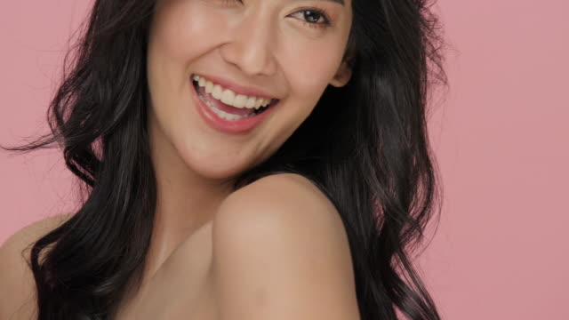 いちゃつくかわいい女ふざけてカメラのためにポーズとスローモーションでピンクの背景に笑みを浮かべてします。 - スタジオ 日本人点の映像素材/bロール