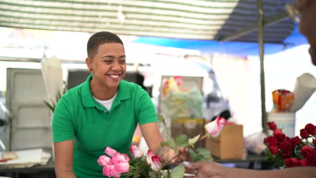 Young florist selling a rose to client