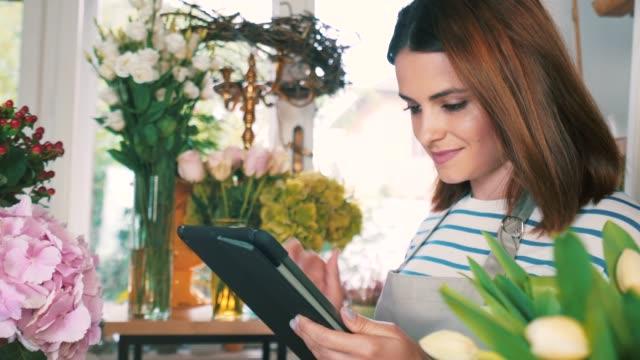unga florist arbetar i hennes butik. - blomstermarknad bildbanksvideor och videomaterial från bakom kulisserna
