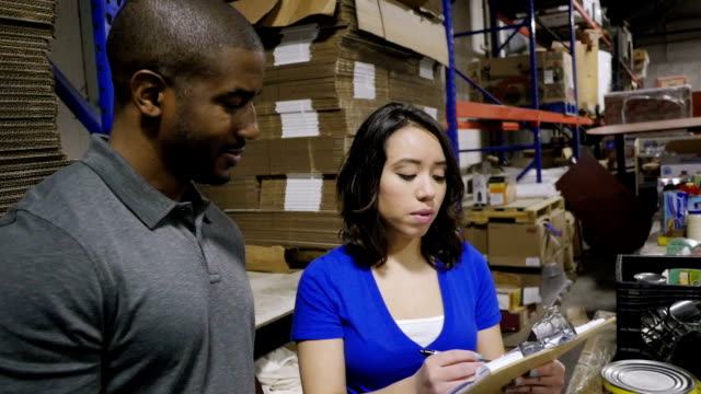 Young food bank manager taking inventory of donated groceries with volunteer in warehouse video
