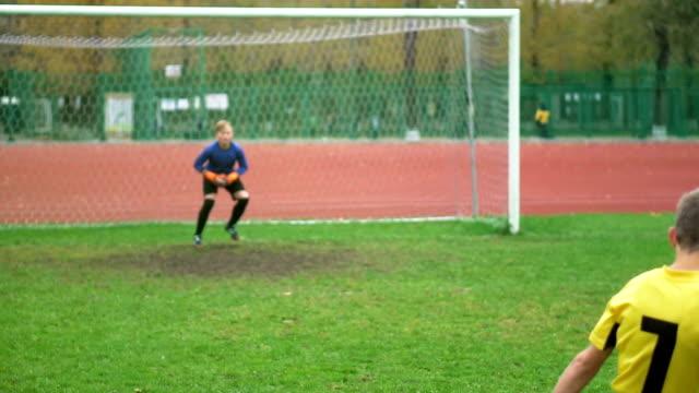 junger fußballspieler den ball im stadion - strafstoß oder strafwurf stock-videos und b-roll-filmmaterial
