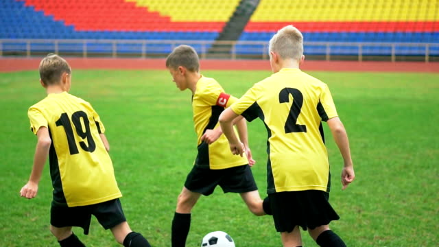 Young football players running with the ball on the pitch video