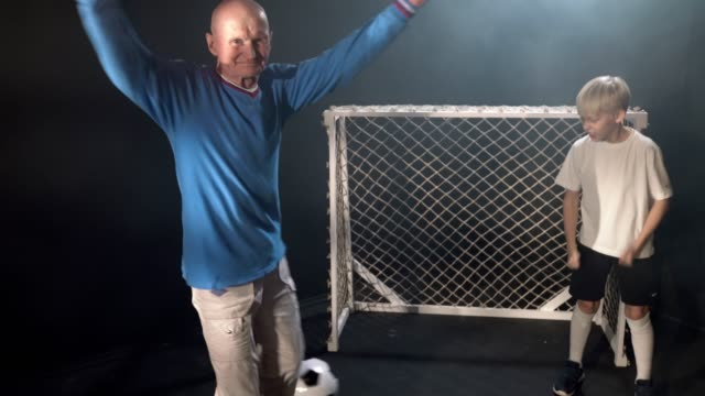 Young Footballer And Old Man Playing Soccer Indoors. Old Man Is Scoring Goal His Head And Rejoicing video