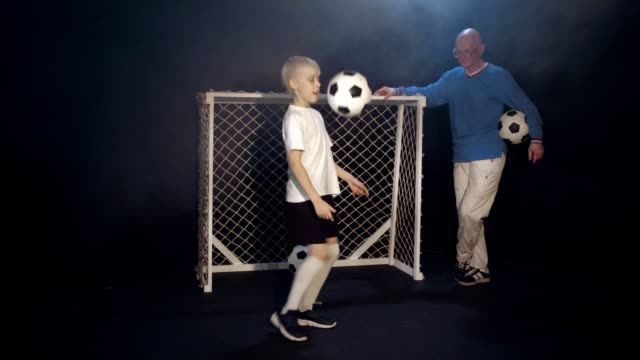 Young Footballer Is Showing His Soccer Stunts To Old Man