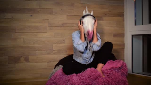 stockvideo's en b-roll-footage met jonge freaky vrouw in grappige unicorn masker - teenager animal